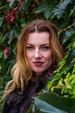 Mujer encantadora joven con el pelo largo que se coloca cerca de la pared con las hojas decorativas del día salvaje del otoño de  Fotos de archivo libres de regalías