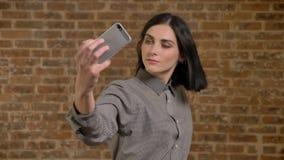 Mujer encantadora joven con el pelo marrón corto que toma el selfie con el teléfono y que agita su pelo, fondo de la pared de lad almacen de metraje de vídeo