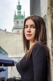 Mujer encantadora joven con el pelo rizado largo, dando un paseo entre la ciudad vieja de la arquitectura de Lviv en vestido del  Foto de archivo