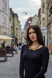 Mujer encantadora joven con el pelo rizado largo, dando un paseo entre la ciudad vieja de la arquitectura de Lviv en vestido del  Imagen de archivo