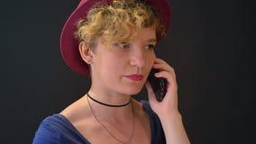 Mujer encantadora joven con el pelo rubio rizado que habla en el teléfono, aislado en fondo oscuro metrajes