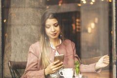Mujer encantadora joven con el teléfono de célula mientras que se sienta solamente en cafetería durante el tiempo libre, femenino imágenes de archivo libres de regalías