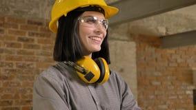 Mujer encantadora joven del arquitecto que mira adelante, sonriendo y cabeceando con confianza, sonriendo, fondo del edificio de  almacen de metraje de vídeo