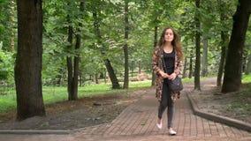 Mujer encantadora joven en chaqueta colorida que camina en parque con los árboles verdes y que mira alrededor, feliz y alegre almacen de metraje de vídeo