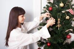 Mujer encantadora que adorna el árbol de navidad con las bolas. Imagen de archivo libre de regalías