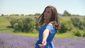 Mujer encantadora que camina en campo floreciente de la lavanda almacen de metraje de vídeo