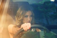 Mujer encantadora que conduce el coche y que mira lejos Imagenes de archivo