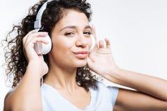 Mujer encantadora que escucha la música y poner mala cara Fotos de archivo