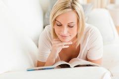 Mujer encantadora que lee un compartimiento Imagenes de archivo