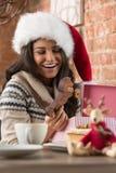 Mujer encantadora que lleva el regalo de la Navidad de la abertura del sombrero de Santa Claus Imagen de archivo