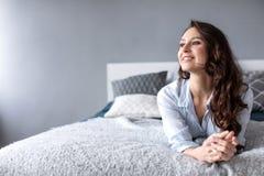 Mujer encantadora que miente en la cama y que mira para vaciar el espacio de la copia por la mañana imagenes de archivo