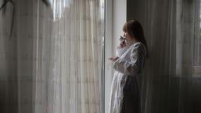 Mujer encantadora que mira hacia fuera la ventana almacen de metraje de vídeo