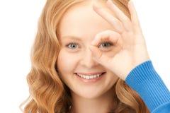 Mujer encantadora que mira a través del agujero de los dedos Imagen de archivo