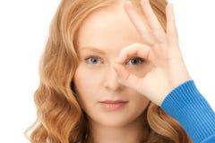 Mujer encantadora que mira a través del agujero de los dedos Fotografía de archivo libre de regalías