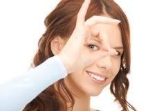 Mujer encantadora que mira a través del agujero de los dedos Fotos de archivo