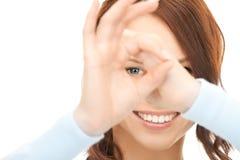 Mujer encantadora que mira a través del agujero de los dedos Foto de archivo libre de regalías