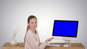Mujer encantadora que presenta algo en la pantalla del ordenador que habla con la exhibición de la maqueta de la pantalla azul de almacen de video