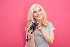 Mujer encantadora que presenta con la cámara de la foto Imagenes de archivo