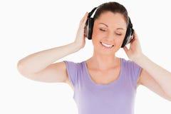 Mujer encantadora que presenta con los auriculares mientras que se coloca Imágenes de archivo libres de regalías