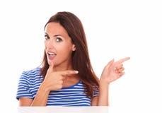 Mujer encantadora que señala a su izquierda Imagen de archivo