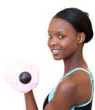Mujer encantadora que se resuelve con pesa de gimnasia Fotos de archivo libres de regalías
