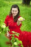 Mujer encantadora que sugiere una manzana Imagenes de archivo