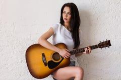 Mujer encantadora que toca la guitarra acústica Foto de archivo