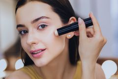Mujer encantadora que usa el palillo del lápiz corrector mientras que pone maquillaje imágenes de archivo libres de regalías