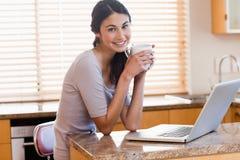 Mujer encantadora que usa una computadora portátil mientras que bebe una taza de un café Imagen de archivo libre de regalías