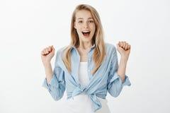 Mujer encantadora triunfante del positivo con el pelo rubio, aumentando las manos y los puños de apretón del entusiasmo contento, fotografía de archivo