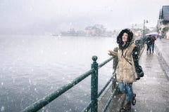 Mujer encendido a orillas del lago mientras que nieva Imagen de archivo libre de regalías