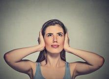 Mujer enfadada, infeliz, subrayada que cubre sus oídos, mirando para arriba Fotos de archivo libres de regalías