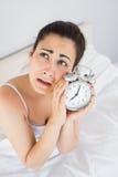 Mujer enfadada que sostiene un despertador en cama Imagenes de archivo