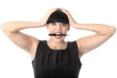 Mujer enfadada subrayada exasperada con Pen In Mouth Imagenes de archivo