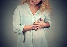 Mujer enferma con el ataque del corazón, dolor que toca su pecho con las manos Imágenes de archivo libres de regalías
