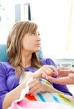 Mujer enferma con el vidrio de agua que miente en un sofá Fotos de archivo libres de regalías