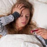 Mujer enferma con fiebre que comprueba su temperatura foto de archivo