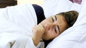 Mujer enferma con gripe en toser de la cama fuerte almacen de metraje de vídeo