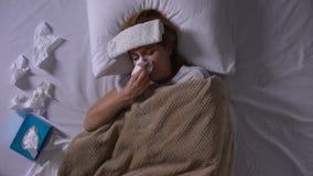 Mujer enferma con la compresa que miente en cama, tosiendo y estornudando, alergia estacional almacen de metraje de vídeo