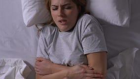 Mujer enferma con la fiebre que miente en la cama, sufriendo de síntomas de la gripe, epidemia almacen de video