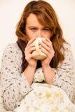 Mujer enferma con la taza de consumición del feaver de té caliente debajo de la manta Imagenes de archivo