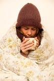 Mujer enferma con la taza de consumición del feaver de té caliente debajo de la manta Fotos de archivo libres de regalías