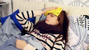 Mujer enferma con la toalla mojada en la frente compresa almacen de video