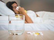 Mujer enferma cubierta con una manta que miente en cama con alta fiebre fotos de archivo