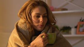 Mujer enferma cubierta en la manta que bebe el té caliente, tratamiento no tradicional almacen de video
