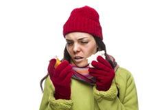 Mujer enferma de la raza mixta con la nariz que sopla de las botellas vacías de la medicina Foto de archivo libre de regalías