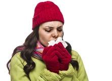 Mujer enferma de la raza mixta que sopla su nariz dolorida con el tejido Fotografía de archivo libre de regalías