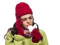 Mujer enferma de la raza mixta que sopla su nariz dolorida con el tejido Fotos de archivo libres de regalías
