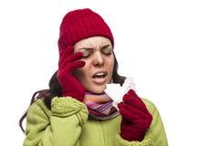 Mujer enferma de la raza mixta que sopla su nariz dolorida con el tejido Imagen de archivo