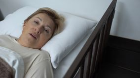 Mujer enferma del pensionista que miente en lecho de enfermo y cara de cierre con la mano de temblor, miedo metrajes